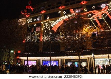 PARIS, FRANCE - NOVEMBER 23, 2014:  Christmas decoration (Magical journey by Burberry) in the windows of Printemps department store attracts Parisian children, tourists and shopping crowd. - stock photo