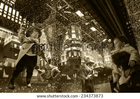 PARIS, FRANCE - NOVEMBER 23, 2014:  Christmas decoration (Magical journey by Burberry) in the windows of Printemps department store attracts Parisian children and tourists. - stock photo