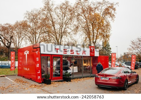 PARIS, FRANCE - NOVEMBER 29, 2014: Customer admiring new Tesla Model S at showroom  in Paris, France. Tesla is an American company that designs, manufactures, and sells electric cars - stock photo