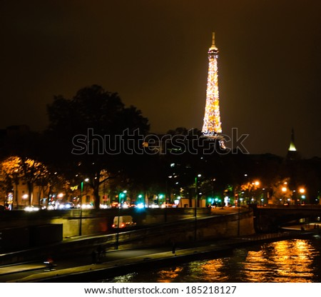 PARIS, FRANCE - NOVEMBER 17, 2013: Glowing defocused Eiffel Tower over Seine river. France. Eiffel tower is the most visited paid monument in the world with over 7 million visitors a year. - stock photo