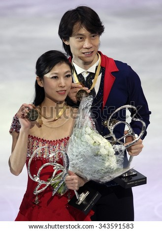 PARIS, FRANCE - NOVEMBER 16, 2013: Qing PANG / Jian TONG of China pose during the victory ceremony after winning gold medals at Trophee Bompard ISU Grand Prix at Palais Omnisports de Bercy. - stock photo