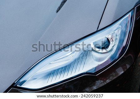 PARIS, FRANCE - NOVEMBER 29, 2014: The Tesla Motors Inc. frontal view advanced xenon head-lights of the Model S electric vehicle displayed at the company's showroom in Paris, France - stock photo