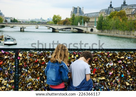 PARIS, FRANCE - OCTOBER 4, 2014: Unidentified boy and girl on Love locks bridge in Paris. Ritual of affixing padlocks, as symbol of love, to bridge is spread in Europe from 2000s. - stock photo