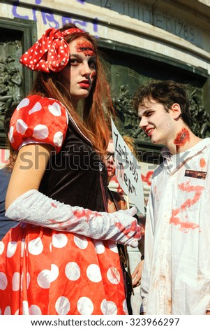 PARIS, FRANCE - OCTOBER 3, 2015: Young zombie woman with sign in her hand (Zomb sexy team) during Zombie parade at Place de la Republique. Zombie Walk is an annual event in Paris. - stock photo