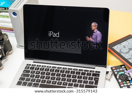 PARIS, FRANCE - SEP 10, 2015: Apple Computers website on MacBook Pro Retina in a creative room environment with Tim Cook and iPad - stock photo