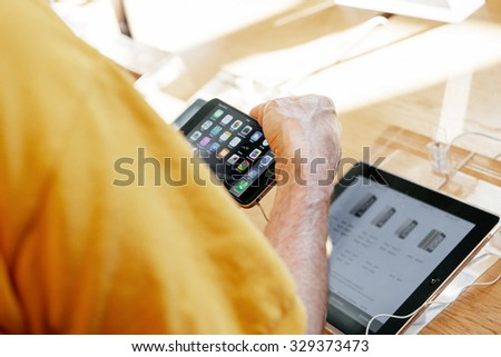 PARIS, FRANCE - SEP 20, 2014: Man comparing the new Apple iPhone 6 and iPhone 6 Plus during the sales launch of the latest Apple Inc. - stock photo