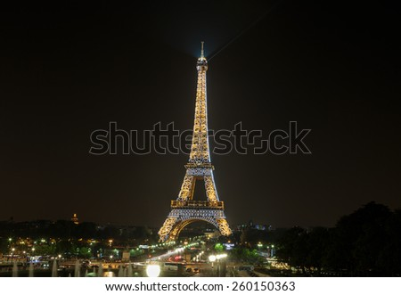 PARIS, FRANCE - SEPTEMBER 11, 2014 : Eiffel Tower brightly illuminated at night in September in Paris. The Eiffel tower is the most visited monument of France. - stock photo
