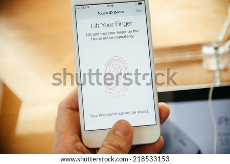 PARIS, FRANCE - SEPTEMBER 20, 2014: Hand holding a iPhone 6 Plus displaying the new Touch ID App with  fingerprint option during the sales launch of the latest Apple Inc. smartphones  - stock photo