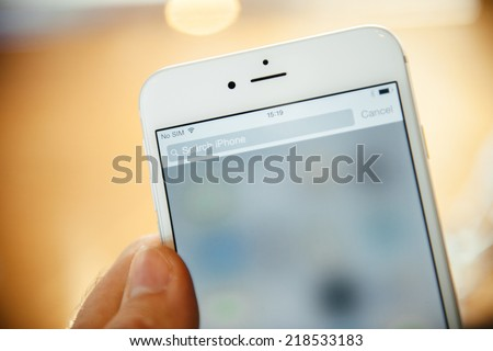 PARIS, FRANCE - SEPTEMBER 20, 2014: Hand holding a iPhone 6 Plus displaying the Search this iPhone field during the sales launch of the latest Apple Inc. smartphones at the Apple store - stock photo