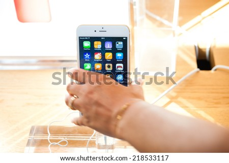 PARIS, FRANCE - SEPTEMBER 20, 2014: Hand holding a iPhone 6 Plus during the sales launch of the latest Apple Inc. smartphones at the Apple store in Paris, France - stock photo