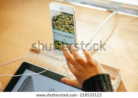 PARIS, FRANCE - SEPTEMBER 20, 2014: Kid hand playing a game on the new iPhone 6 Plus in Apple Store during the sales launch of the latest Apple Inc. smartphones at the Apple store in Paris, France - stock photo