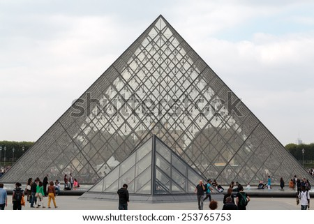 PARIS, FRANCE - SEPTEMBER 11 , 2014: The Glass  Pyramid in Louvre Paris, France. It serves as the main entrance to the Louvre Museum. Completed in 1989 it has become a landmark of Paris.  - stock photo
