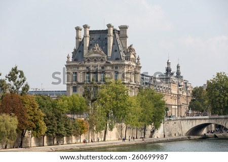 PARIS, FRANCE - SEPTEMBER 7, 2014: The Louvre and  the Seine River in Paris .  Louvre is one of the biggest Museum in the world, receiving more than 8 million visitors each year. Paris,France  - stock photo