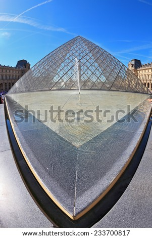 PARIS, FRANCE - SEPTEMBER 8, 2012: The world-famous entrance to  Louvre - the glass pyramid and spectacular fountain. Picture taken Fisheye lens - stock photo