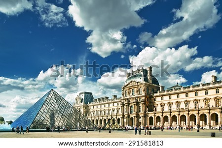 PARIS, FRANCE - 8 SEPTEMBER 2013: View of the large glass pyramid and the main courtyard of the Louvre Museum on 8 SEPTEMBER 2013. The Louvre Museum is one of the largest museums of the world. - stock photo
