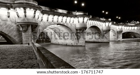 Paris illuminated bridge at night. Famous Pont Neuf, the oldest standing bridge over the river Seine. Construction began in 1578 and was completed in 1603. - stock photo