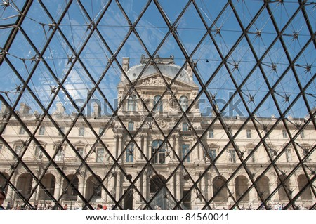 PARIS - JULY 6: Louvre museum and Pyramid before sunset on July 06, 2011 in Paris. Louvre is most visited museum in the world with 8.5 million visitors per year. - stock photo