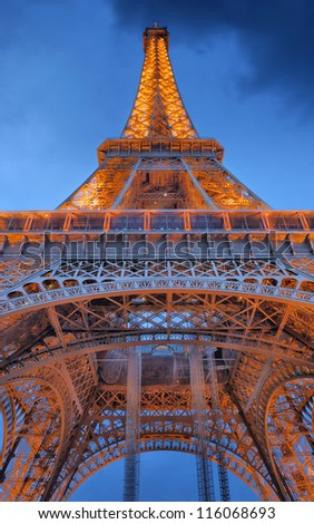 PARIS - JULY 30: The Eiffel Tower from below upwards in the evening on July 30, 2012 in Paris, France. The Eiffel Tower lit by more than 350 lamps mounted within the structure of the tower itself. - stock photo