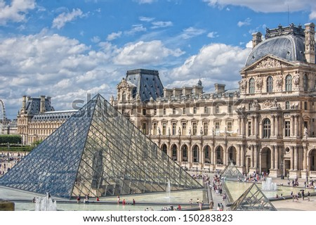 PARIS - JULY 21: The Louvre museum and the pyramid on July 21, 2013 in Paris, France. The Louvre was once a palace and is now a museum. The pyramid serves as an entrance to the museum. - stock photo