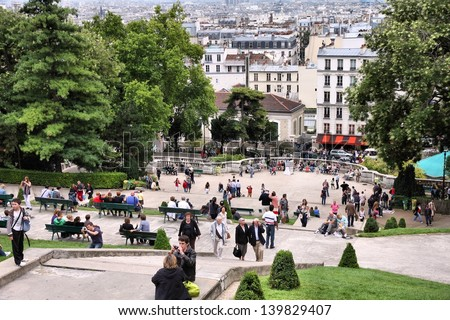 PARIS - JULY 22: Tourists stroll in Montmartre district on July 22, 2011 in Paris, France. Monmartre area is popular among tourists in Paris, the most visited city worldwide. - stock photo