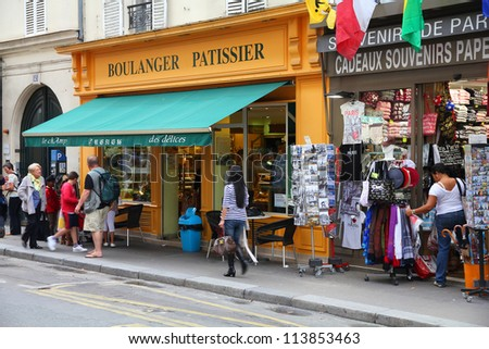 PARIS - JULY 21: Tourists walk past a souvenir store on July 21, 2011 in Paris, France. Paris is the most visited city in the world with 15.6 million international arrivals in 2011. - stock photo