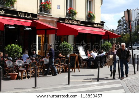 PARIS - JULY 24: Tourists walk past Villa Borghese cafe on July 24, 2011 in Paris, France. Paris is the most visited city in the world with 15.6 million international arrivals in 2011. - stock photo