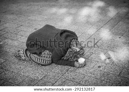 PARIS - JUNE 2 : An unidentified female begs on the street in the Champs-Elysees on June 2, 2015 in Paris, France. The number of beggars is considerably higher due to the current economics.  - stock photo