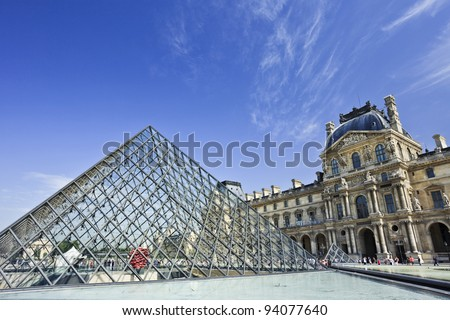 PARIS - JUNE 28, 2011. Glass Pyramid at the Louvre Museum on June 28, 2011. The museum was inaugurated in 1739. However, due to some infrastructural problems, it was shut down for 5 years. - stock photo