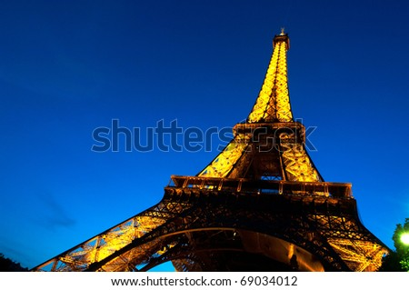 PARIS - JUNE 23 : Illuminated Eiffel tower at night sky June 23, 2010 in Paris. The Eiffel tower is one of the most recognizable landmarks in the world. - stock photo