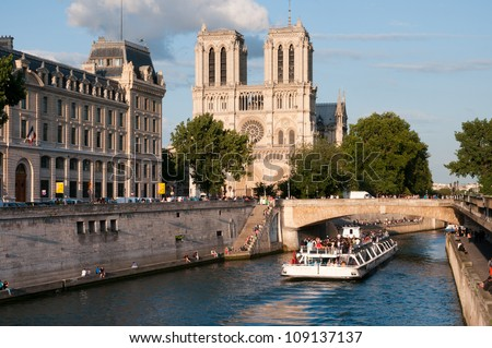 PARIS - JUNE 30: Tourists enjoy a boat trip on Seine river near Notre Dame cathedral on June 30, 2012 in Paris, France. - stock photo