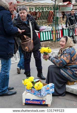 PARIS - MARCH 10: An unidentified smiling senior woman sells yellow narcissus to buyers at market on March 10, 2013 in Paris, France. Narcissus is a traditional Easter flower in European countries. - stock photo