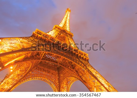 PARIS - MARCH 14: Eiffel Tower brightly illuminated at dusk on Mar 14, 2015 in Paris. The Eiffel tower is the most visited monument of France. - stock photo