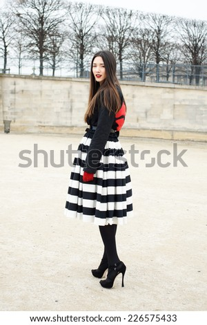 PARIS - MARS 5, 2013: Stylish European girl with black and white stripped skirt in the Tuileries Garden. Paris Fashion Week: Ready to Wear 2013/2014 is held from February 26 to March 6, 2013. - stock photo