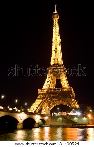 PARIS - MAY 17 : Illuminated Eiffel tower at night overlooking the River Seine May 17, 2009 in Paris. The Eiffel tower is one of the most recognizable landmarks in the world. - stock photo