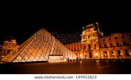 PARIS - MAY 15: The Louvre Pyramid shines at night on May 15, 2010 in Paris, France. The museum is housed in the Louvre Palace (Palais du Louvre) which began as a fortress built in the 12th century. - stock photo
