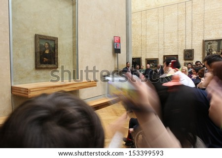 """PARIS - MAY 3: Visitors take photo of Leonardo DaVinci's """"Mona Lisa"""" at the Louvre Museum, May 3, 2013 in Paris, France. The painting is one of the world's most famous - stock photo"""