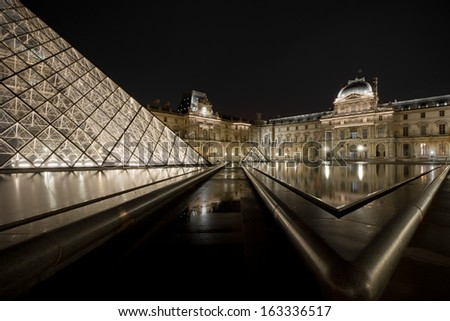 PARIS - NOV 2: Louvre Pyramid at dusk on November 2, 2013 in Paris, France. The Louvre houses France's art collection and is the biggest Museum in Paris displaying over 60,000 sq meters of space. - stock photo