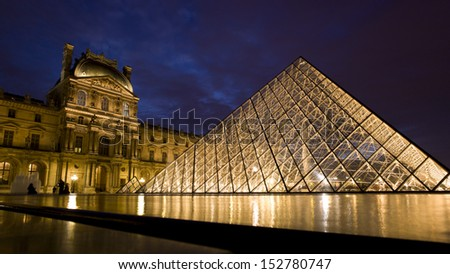 PARIS - NOV 21: Louvre pyramid shining at dusk during the Winter Exhibition on November 21,2012 in Paris.Louvre is the biggest Museum in Paris displayed over 60,000 square meters of exhibition space.  - stock photo