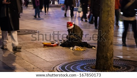 PARIS - NOV 30: Old man in Santa Claus hat begs on Avenue des Champs Elysees on November 30, 2013 in Paris, France. Beggars work in the most popular shopping and tourist hot spots of Paris. - stock photo