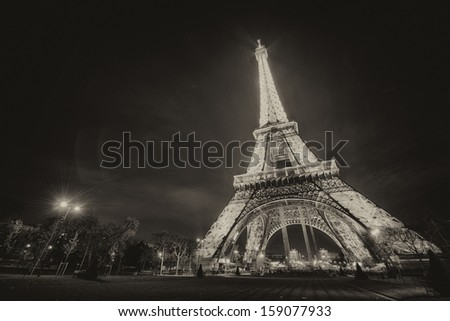 PARIS - NOV 30: Tourists walk underneath Eiffel Tower at dusk, November 30, 2012 in Paris. The Eiffel tower is the highest monument and also most visited monument of France - stock photo