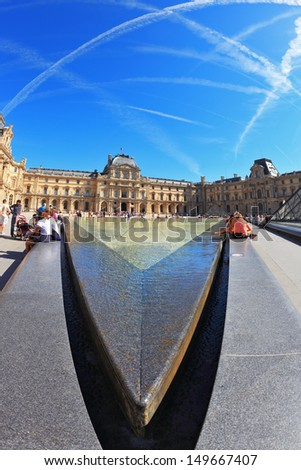 PARIS - SEPT 8: The world-famous entrance to the Louvre - fountain September 8, 2012 in Paris. Tourists resting on a granite fence fountain. Picture taken Fisheye lens - stock photo