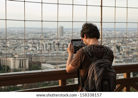 PARIS - SEPTEMBER 10: A tourist visiting the Eiffel tower is taking panoramic photo of Paris by using his Apple iPad tablet computer in the warm autumn on September 10, 2011 in Paris, France.  - stock photo