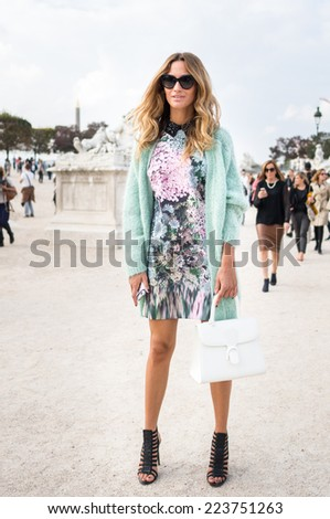 PARIS - SEPTEMBER 30, 2014: Stylish european woman with flower pattern skirt in the Tuileries Garden. Paris Fashion Week: Ready to Wear 2014/2015 is held from September 23 to October 1, 2014. - stock photo