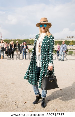 PARIS - SEPTEMBER 30, 2014: Stylish european woman with green dress in the Tuileries Garden. Paris Fashion Week: Ready to Wear 2014/2015 is held from September 23 to October 1, 2014. - stock photo