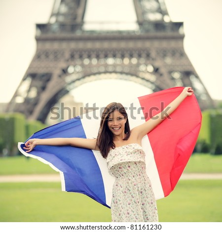 Paris woman holding French flag by the Eiffel Tower in Paris. Tourist on travel in europe. - stock photo