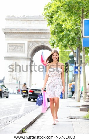 Paris woman shopping walking on Champs-Elysees with Arc de Triomphe in the background. Beautiful happy young woman tourist shopping during her travel in Paris, France - stock photo