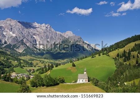 Parish church of Dienten on a hill in foreground, view over the village Dienten to the Hochkoenig mountain in background, Pinzgau, Salzburg, Austria - stock photo