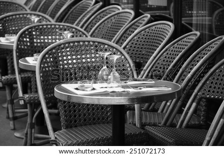 Parisian cafe terrace. Selective focus on the glasses. Aged photo. Black and white. - stock photo