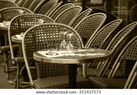Parisian cafe terrace. Selective focus on the glasses. Aged photo. Sepia. - stock photo
