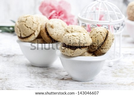 Parisian macaroons on white wooden table. Pink carnation flowers in the background. - stock photo